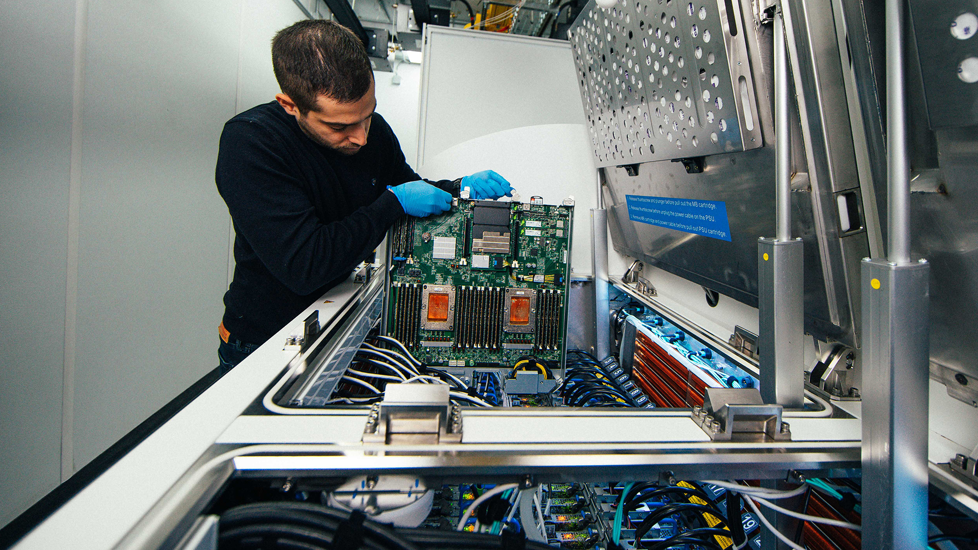 Ioannis Manousakis, a principal software engineer with Azure, removes a server blade from a two-phase immersion cooling tank at a Microsoft data center.