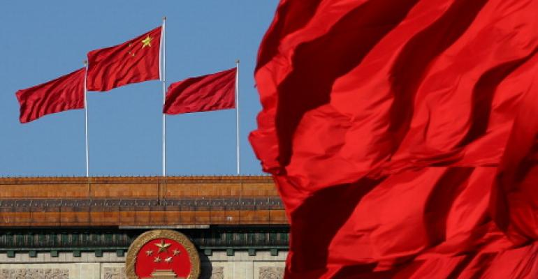 Red flags flutter in the wind near the Chinese national emblem outside the Great Hall of the People in Beijing, China.