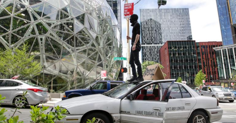 """Protesters block traffic as they participate in a """"car caravan"""" protest at the Amazon Spheres to demand the Seattle City Council tax the city's largest businesses in Seattle, Washington on May 1, 2020."""