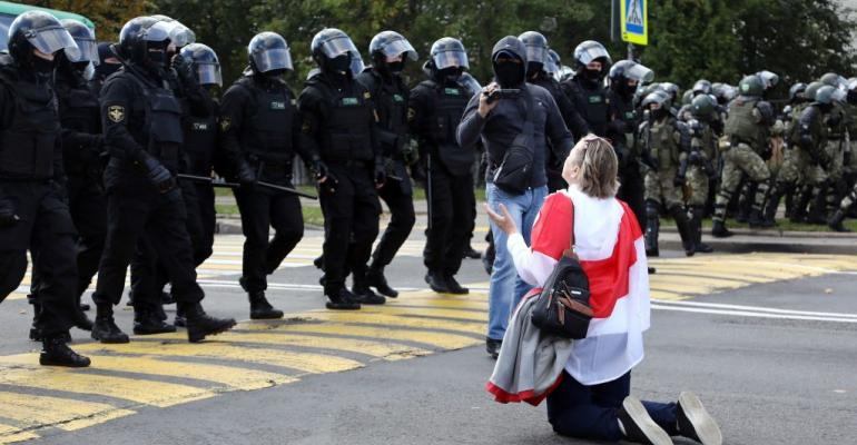 A woman kneels in front of law enforcement officers during a rally to protest against the presidential election results in Minsk on September 13, 2020.