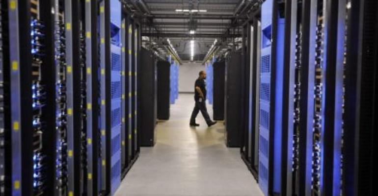 An employee walks past servers in the Facebook data center in Forest City, North Carolina.