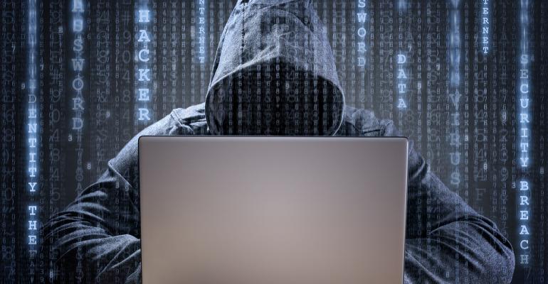 hacker wearing a hood on a laptop