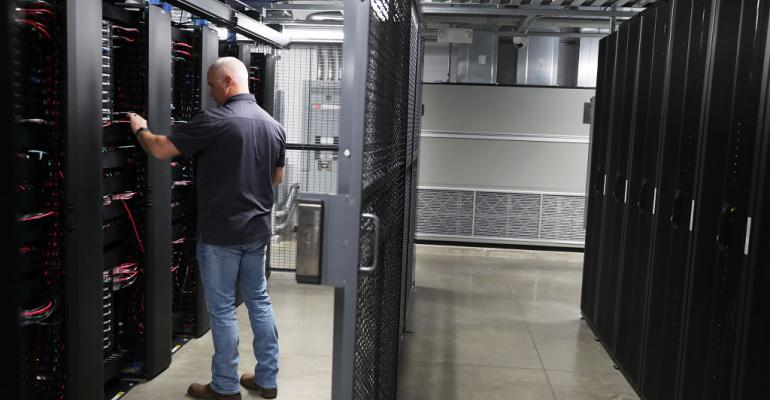 A staff member works among the racks and network switches in the data center of LightEdge Solutions in Altoona, Iowa.