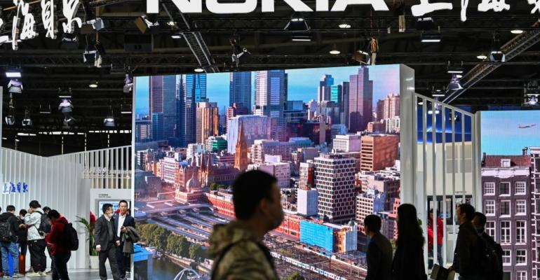 People walk past the Nokia booth during the Mobile World Congress in Shanghai on February 23, 2021.