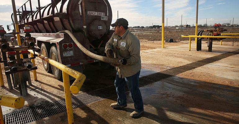 An oilfield worker fills his truck with water before heading to a drilling site in the Permian Basin oilfield in the oil town of Andrews, Texas, in 2016.