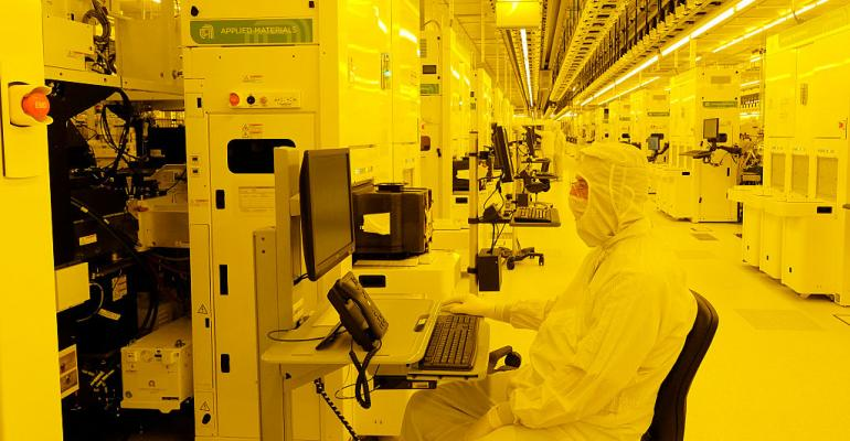 System engineers supervise the production line for 300mm wafers in a clean room at the GlobalFoundries semiconductor manufacturing plant in Dresden, Germany, in 2015.