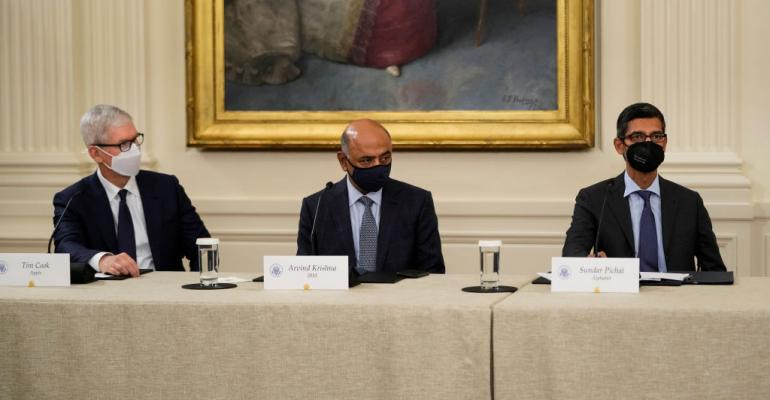 Apple CEO Tim Cook, IBM CEO Arvind Krishna and Google CEO Sundar Pichai listen as U.S. President Joe Biden speaks during a meeting about cybersecurity in the East Room of the White House.