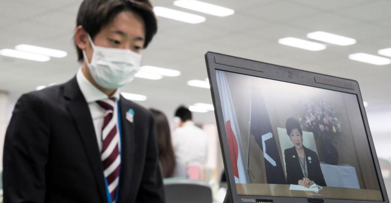 A newly hired Tokyo Metropolitan Government employee watches a computer screen displaying a live steam of a speech by Tokyo Governor Yuriko Koike on April 01, 2020.