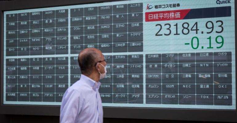 A man walks pass an empty stock board which normally shows stock prices at the Tokyo Stock Exchange on October 01, 2020 in Tokyo. On that morning the exchange suspended all trading after encountering a technical issue that morning.