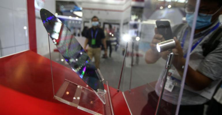 A visitor takes photos of TSMC silicon wafer at the 2020 World Semiconductor Conference in Nanjing, in China's eastern Jiangsu province, on August 26, 2020.