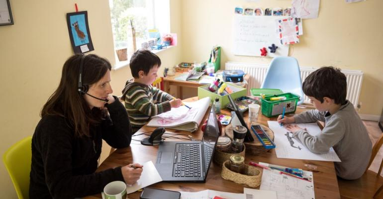 A Marsden, England, regional council employee works from home as her children study in March 2020.