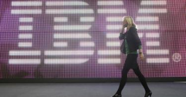 A young woman walks past the IBM logo at the 2009 CeBIT technology trade fair in Hanover, Germany.