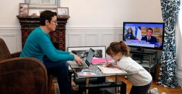 A woman telecommutes from her home in Paris with her daughter playing at home instead of being in school due to office and school closures in response to the Coronavirus pandemic in March 2020.