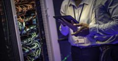 IT engineers with a digital tablet talking next to server cables stock photo.jpg