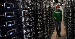 """A worker controls batteries in an electricity storage container near Dijon, France, part of """"Ringo,"""" an energy storage project. (September 2020)"""