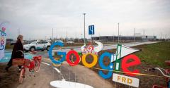 A woman passes by a Google themed barrier in front of a Google data center in Fredericia, Denmark (November 2020)