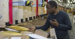 Postal Service employees perform spot checks to ensure packages are properly handled and sorted.
