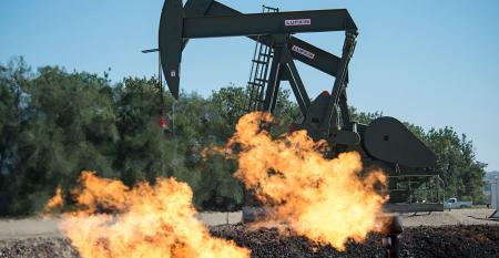 Flaring natural gas burns by jack pumps at an oil well near Buford, North Dakota in the Bakken oil fields.