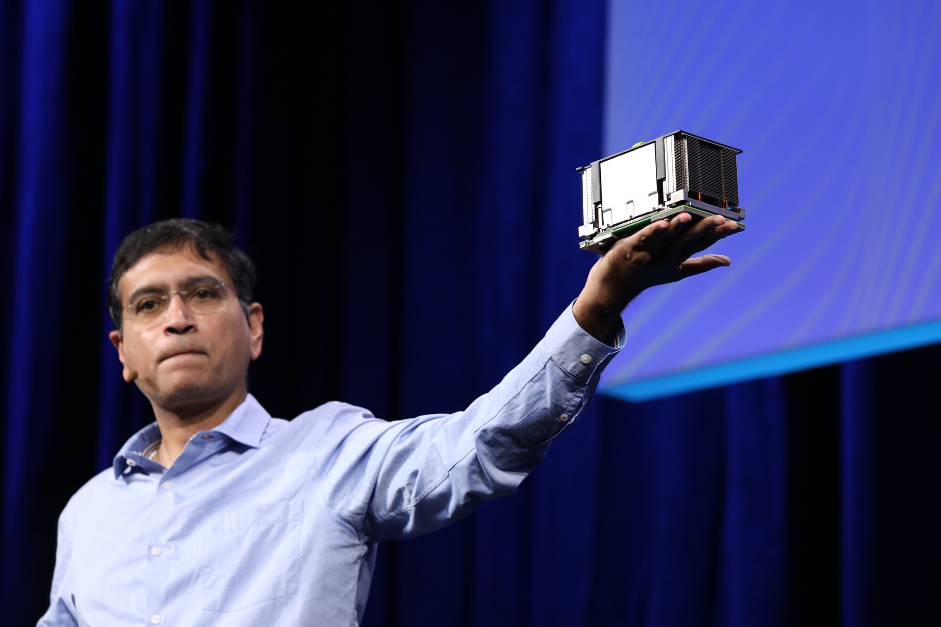 Vijay Rao, Facebook director of technology and strategy, holding up an OCP accelerator module during a keynote at the 2019 OCP Summit