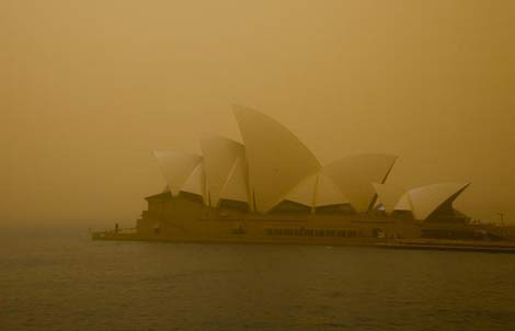 The view of the Sydney Opera House is obscured by red dust from a major dust storm that has engulfed the city.