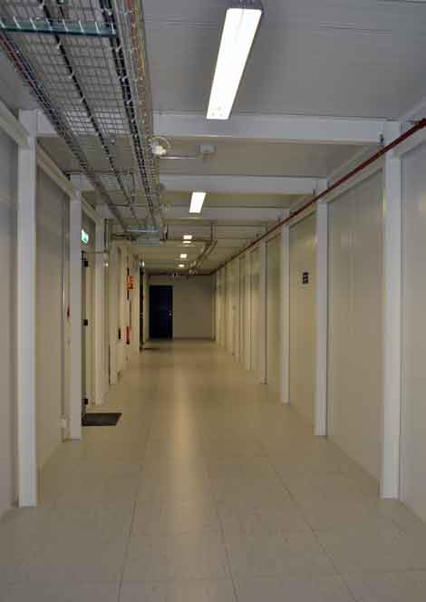 This photo gives an idea of the length of part of the Verne Global data center. Pipes and cables run through the hallway. The door to the data hall is marked with prohibitions, such as no photography, no eating and drinking, and so on. (Photo by Colleen Miller.)