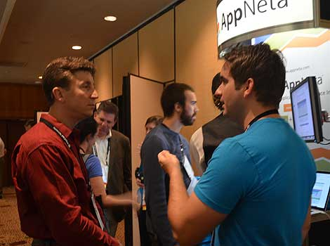 A representative from AppNeta, which produces application and network performance management tools, speaks with a participant. AppNeta was launched in early 2011, by the team and technology of Apparent Networks. AppNeta is headquartered in Boston, (Photo by Colleen Miller.)