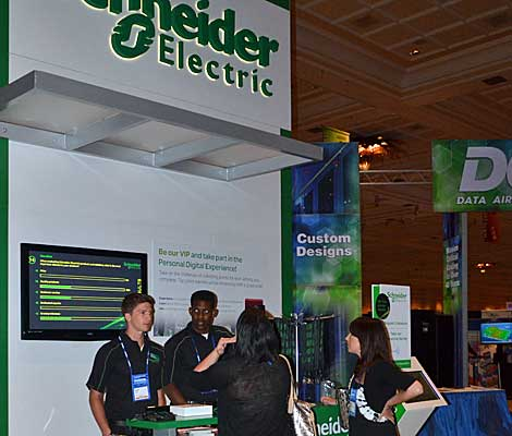 Schneider Electric staff answered questions at the booth in the Data Center World exhibit hall on Wednesday. (Photo by Colleen Miller.)