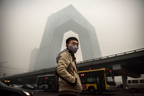 A Chinese man wears a mask as he waits to cross the road near the CCTV building during heavy smog on November 29, 2014 in Beijing. (Photo by Kevin Frayer/Getty Images)