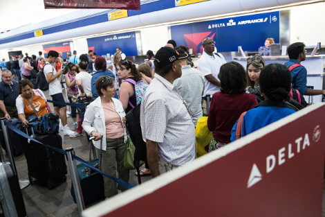 Travelers wait in line at the Delta check-in counter at LaGuardia Airport , August 8, 2016 in the Queens borough of New York City. Delta flights around the globe were grounded and delayed on Monday morning due to a system outage. (Photo by Drew Angerer/Getty Images)