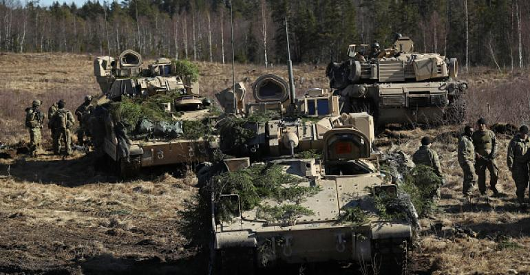 US soldiers stand near their M2A3 Bradley fighting vehicles and an M1 Abrams tank following a joint military combat exercise with Estonian soldiers on March 23, 2017 near Tapa, Estonia.
