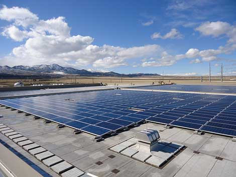 Sun and clouds reflect the large surface of the solar array atop eBay's Topaz Data Center in South Jordan, Utah.