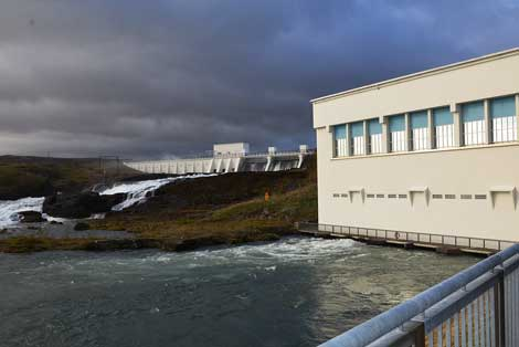 View of the Ljósafossstöð hydroelectric plant in Iceland. Water seen flowing over the dam, at left, while water used in the plant to spin turbines and create electricity is seen coming out from under building at right. The water is flowing from a spring-fed lake, Þingvallavatn, into rivers and streams.  (Photo by Colleen Miller)